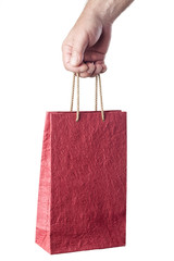 male hand holding red shopping bag isolated on white background