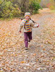 girl runs in autumn park