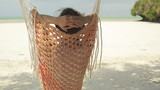 Woman relaxing on hammock on amazing exotic beach