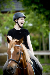 Young girl riding her brown horse outdoors and smiling