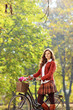 Beautiful female posing in a park with a bike