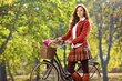 Beautiful young woman posing in a park with a bike