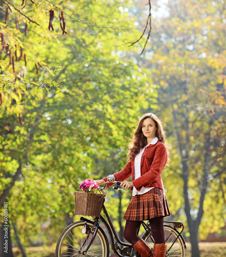 Beautiful female posing in a park with her bicycle