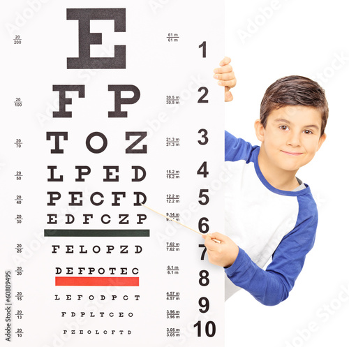 Little boy pointing on an eyesight test with stick