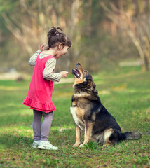 Happy little girl talking to dog