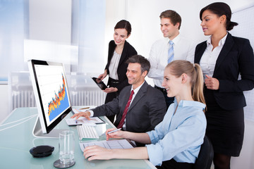 Businesspeople Looking At Graph On Computer