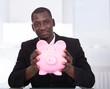 Businessman Holding Piggybank