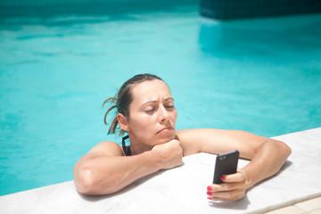 Frau mit Handy angenervt am Pool