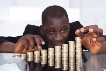 Businessman Stacking Coins In A Row
