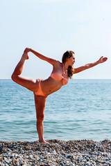 Fit woman in a bikini doing yoga at the seaside