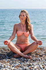 Serene young blond woman meditating on the beach