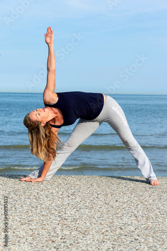 Athletic woman doing yoga training on the beach