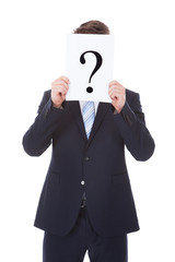 Businessman Holding Question Mark Sign In Front Of Face