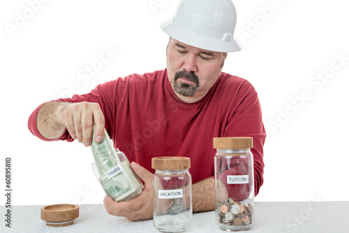 Unhappy construction worker paying the taxes