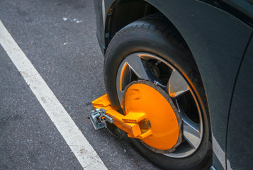 Yellow wheel clamp locked with messing lock on an illegally park