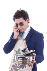 man with an apron holding a cooking pot and talking over phone