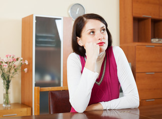unhappy brunette woman at table