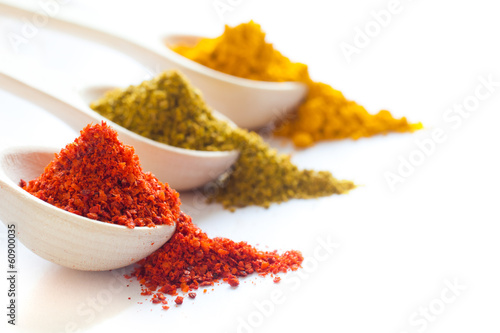Spices in wooden spoons on a white background closeup - 60900035