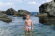 Small boy paddling in a tidal pool at the seaside