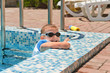 Cute little boy playing at the edge of a pool