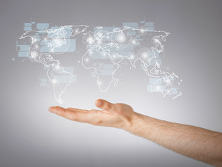 mans hand showing world map