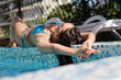 Woman lying sunbathing on the edge of a pool