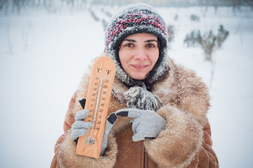 Young woman holding a thermometer in the snow
