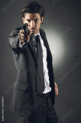 Handsome bodyguard aiming with gun