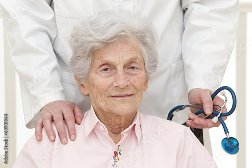 caring doctor with disabled  senior patient in office