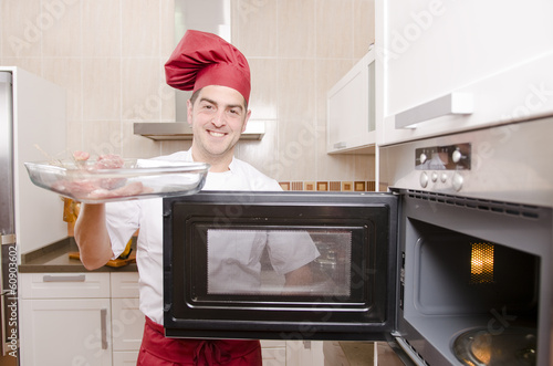 The chef in the kitchen.Cooking with microwave oven