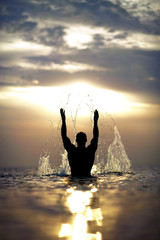 Man's silhouette with raised hands out of the sea with splash