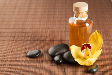essential oil, massage stones and orchid flower