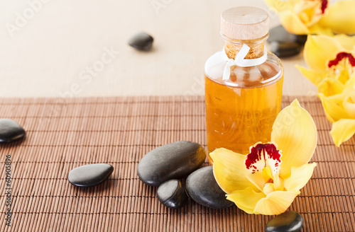 essential oil, massage stones and orchid flowers