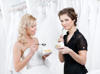 Shop assistant and the bride eat an amasing wedding cake