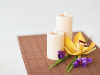 candles, orchid and iris flowers on bamboo mat