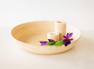 candles and iris flowers in wooden bowel