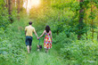 Young couple holding hands and walking with their dog in the for