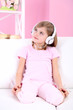 Little girl listening music sitting on sofa in room