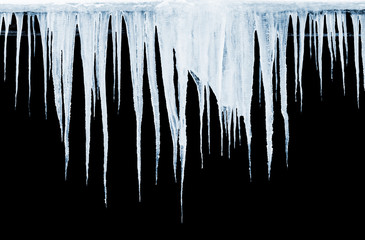 Group of icicles hanging on black background