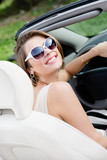 Portrait of pretty woman in sunglasses sitting in the car
