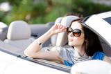 Portrait of dreamy woman wearing sunglasses in the car