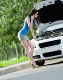 Woman opens car bonnet and tries to repair the broken car