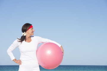 Confident fit senior woman exercising at beach