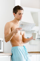 Half-naked man with cup of coffee reads newspaper