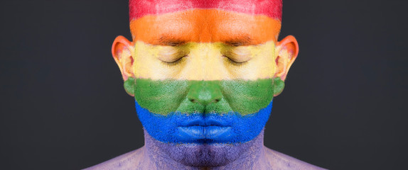 Gay flag painted on the face of a man.
