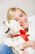 Woman embracing white puppy with red ribbon on the neck
