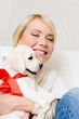 Woman embracing white labrador puppy with red ribbon