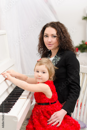 mother and daughter playing on white piano