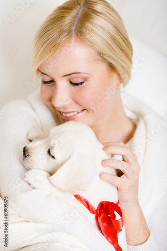 Woman holding white Labrador puppy with red ribbon on the neck