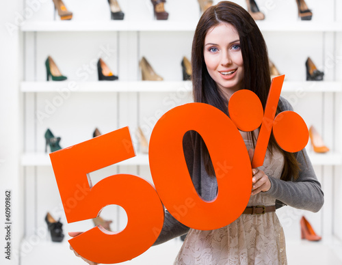 Woman keeps the model of 50% sale on shoes